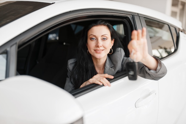 Happy woman shows the key to the new car in showroom. female customer buying vehicle in dealership, automobile sale Premium Photo