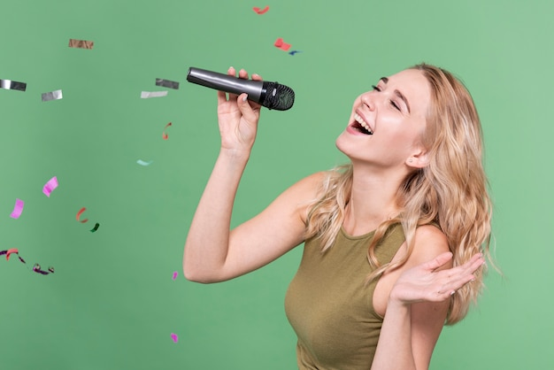 Happy woman singing surrounded by confetti Free Photo