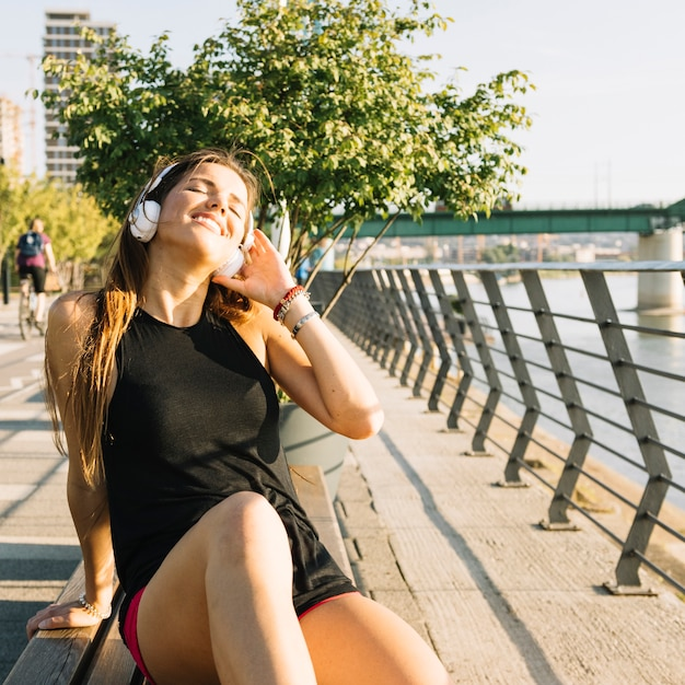 Happy woman sitting on bench listening to music Free Photo