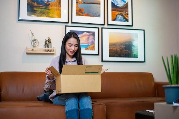 自宅のソファに座って幸せな女カートンボックスを開く Premium写真