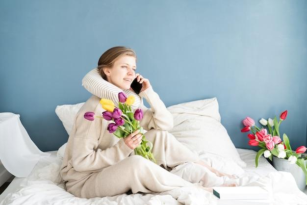 電話で話しているパジャマを着てベッドに座っている幸せな女性、青い壁の背景 Premium写真