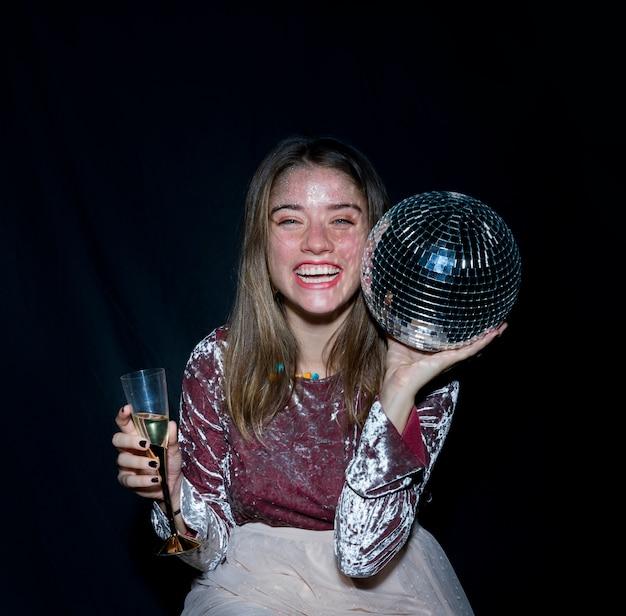 Donna felice che si siede con la palla da discoteca a disposizione Foto Gratuite