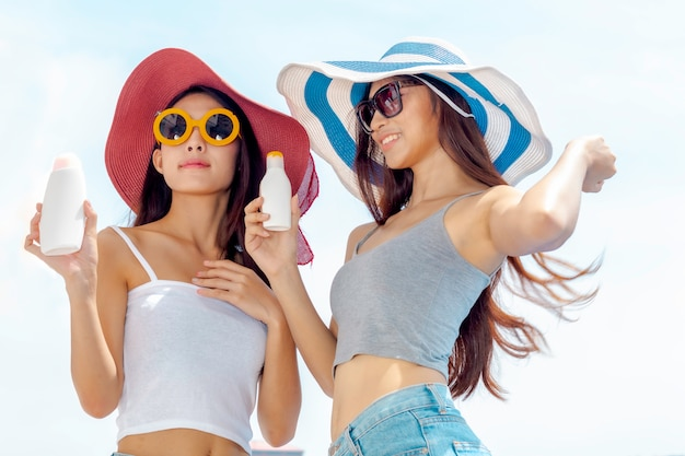 Happy woman smiling in sunglasses holding sunscreen uv protective lotion bottle packaging cosmetic. Premium Photo