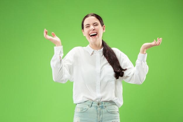 立っていると笑顔の幸せな女性は、緑のスタジオの背景に分離されました。美しい女性の半身像。 無料写真