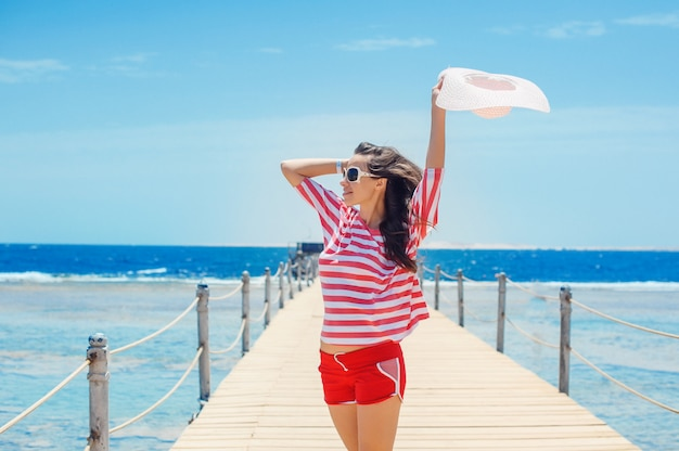 Happy woman standing on pier with big white hat Premium Photo