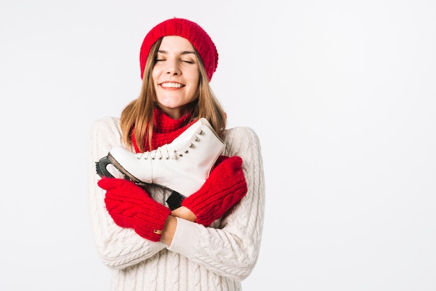 Happy woman in sweater holding skate Free Photo