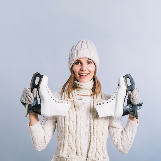 Happy woman in sweater with skates Free Photo