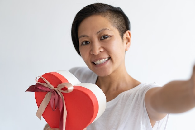 Happy woman taking selfie photo with heart shaped gift box Free Photo