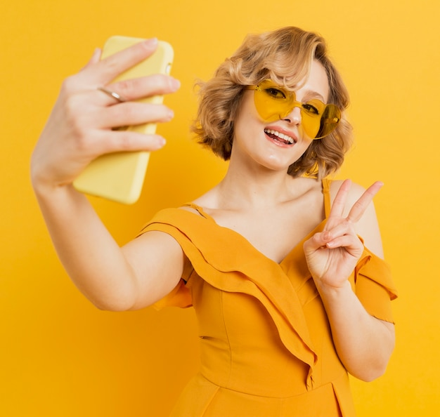 Happy woman taking a selfie while wearing sunglasses Free Photo