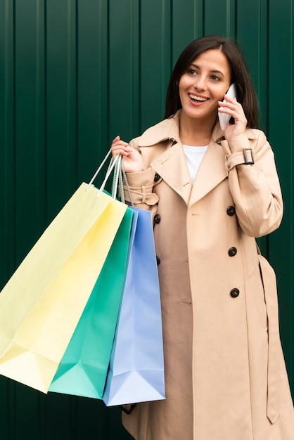 Happy woman talking on the phone outdoors while holding shopping bags Premium Photo