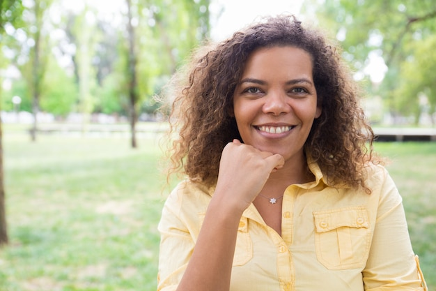 Happy woman touching chin and posing at camera in city park Free Photo
