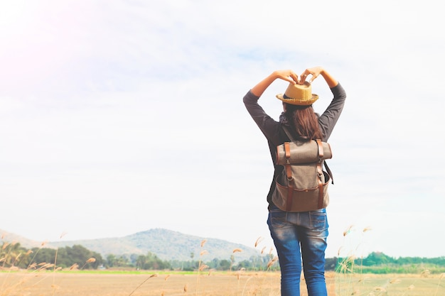 happy woman traveler looking to blue sky and hands love sign