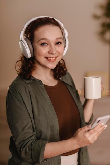 コーヒーを飲みながら自宅でスマートフォンとヘッドフォンを使用して幸せな女性 Premium写真