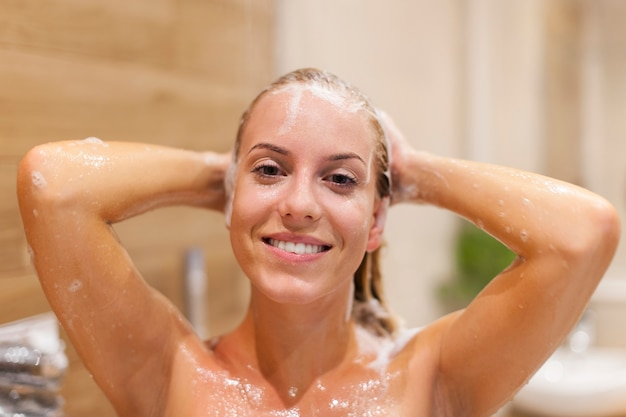 シャワーの下で髪を洗う幸せな女性 無料写真