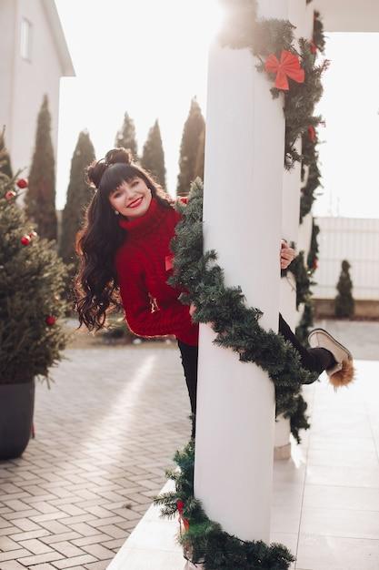 赤いセーターを着て、見掛け倒しで飾られた白い柱の後ろから覗く幸せな女性 無料写真