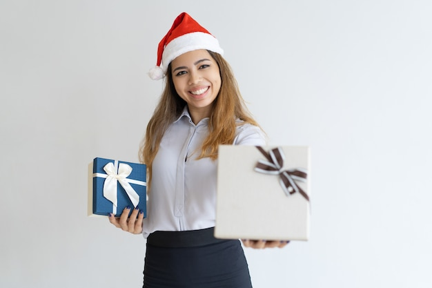 Happy woman wearing santa claus hat and offering gift box Free Photo