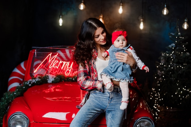 머리에 붉은 활과 아기 소녀와 함께 행복 한 여자는 앉아서 크리스마스 장식과 함께 복고풍 자동차에 재미 프리미엄 사진