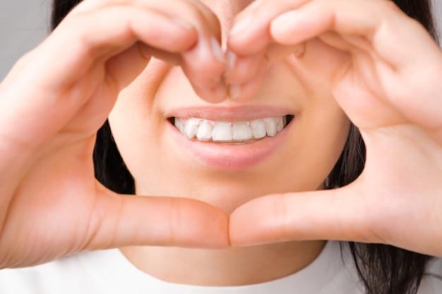 그녀의 이빨에 투명 정렬기에 완벽한 미소로 행복한 여자는 손으로 심장을 보여줍니다 프리미엄 사진