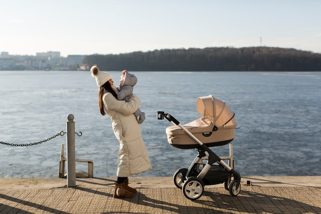 Happy woman with baby on pier Free Photo