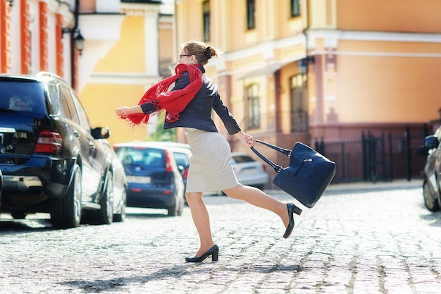 Happy woman with a bag crosses the street Premium Photo