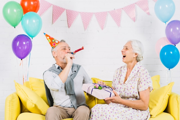 Happy woman with birthday gift looking at her husband blowing party horn Free Photo