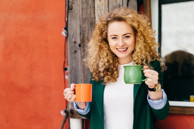 Happy woman with blonde curly fluffy hair charming blue eyes holding two mugs of coffee. Premium Photo