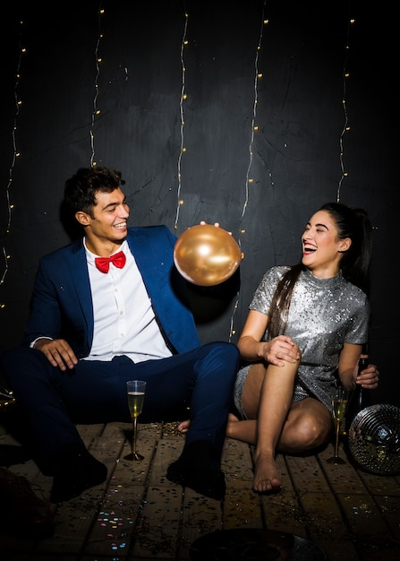 Happy woman with bottle near smiling man with balloon near glasses Free Photo