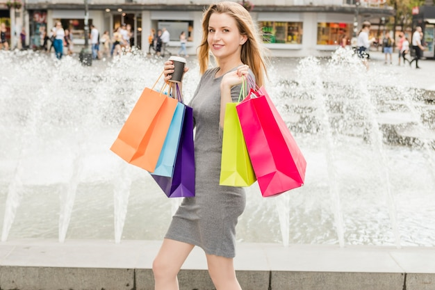 Счастливый женщина с красочными сумок, ходить перед фонтаном Бесплатные Фотографии