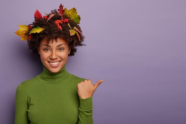 Donna felice con capelli ricci decorati da foglie autunnali, pose indoor, punta il pollice a parte, vestito di verde dolcevita casual, isolato su sfondo viola, sorride ampiamente Foto Gratuite