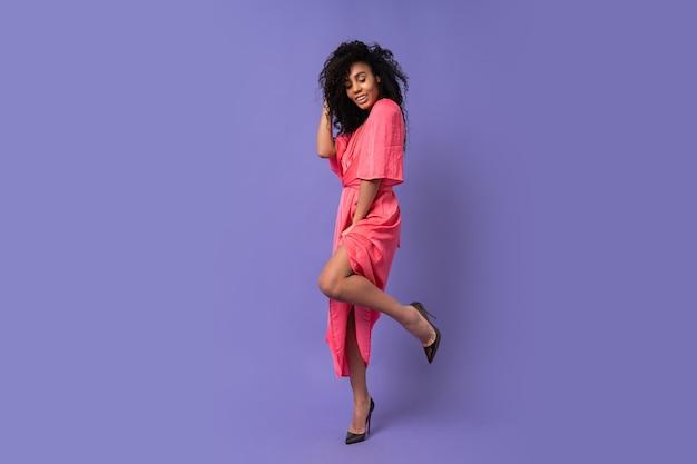 Donna felice con i capelli ricci in posa sul muro viola. indossare un abito da festa elegante. look alla moda primaverile. intera lunghezza. Foto Gratuite