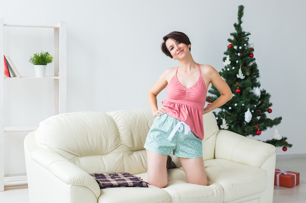 Счастливая женщина с собакой. елка с подарками под ней. украшенная гостиная Premium Фотографии