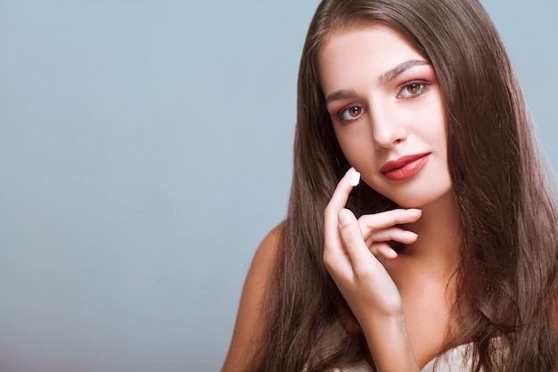 Happy woman with healthy face applying cream under the eyes Premium Photo