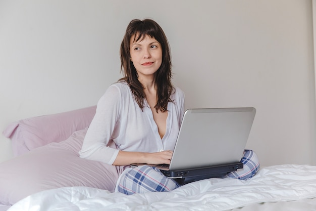 Happy woman with laptop on bed Free Photo