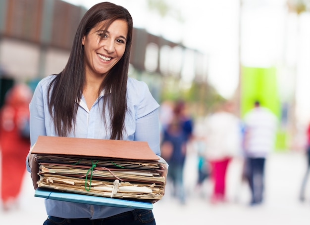Happy woman with many papers and folders Free Photo