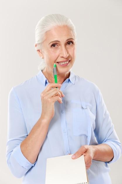 Счастливая женщина с ручкой и тетрадью смотря и усмехаясь Бесплатные Фотографии