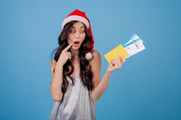 Happy woman with plane tickets and passport wearing santa hat Premium Photo