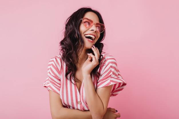 Счастливая женщина с волнистыми каштановыми волосами смеясь. веселая девушка в полосатом розовом наряде улыбается. Бесплатные Фотографии