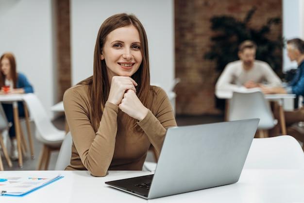 ラップトップに取り組んでいる幸せな女性 Premium写真
