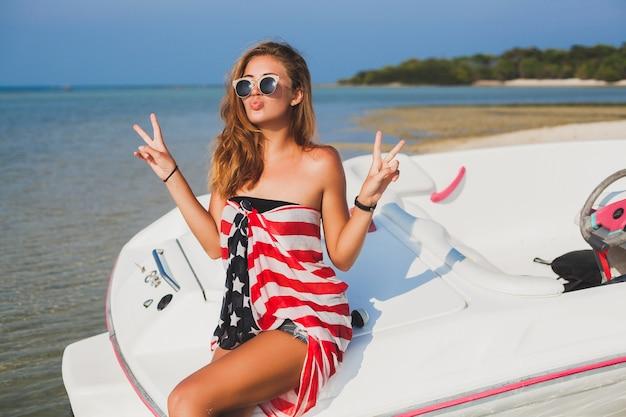 Donna felice avvolta nella bandiera americana in vacanza tropicale estiva in viaggio in barca in mare, festa sulla spiaggia, persone che si divertono insieme, emozioni positive Foto Gratuite