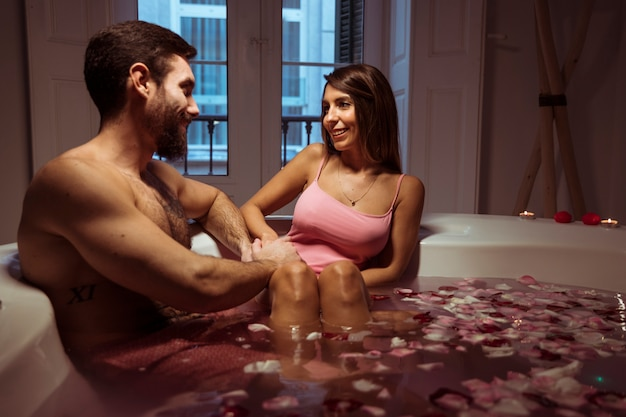 Happy woman and young man in spa tub with water Free Photo