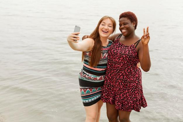 Happy women at the beach taking selfie Free Photo