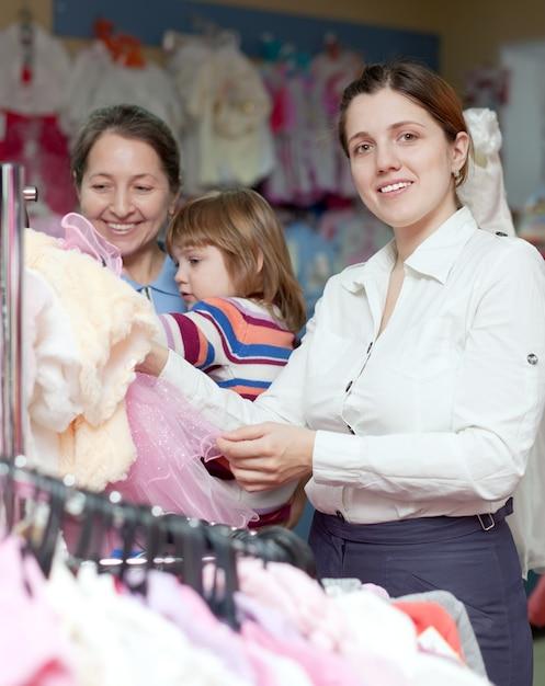 Le donne felici scelgono l'usura nel negozio di abbigliamento. concentrarsi sulla donna Foto Gratuite