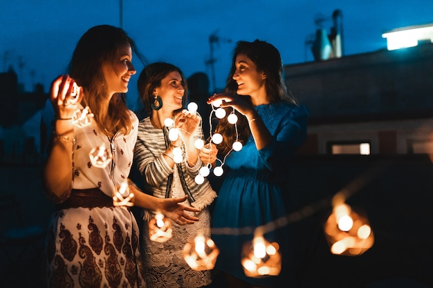Happy women having fun at rooftop party with lights at night Premium Photo