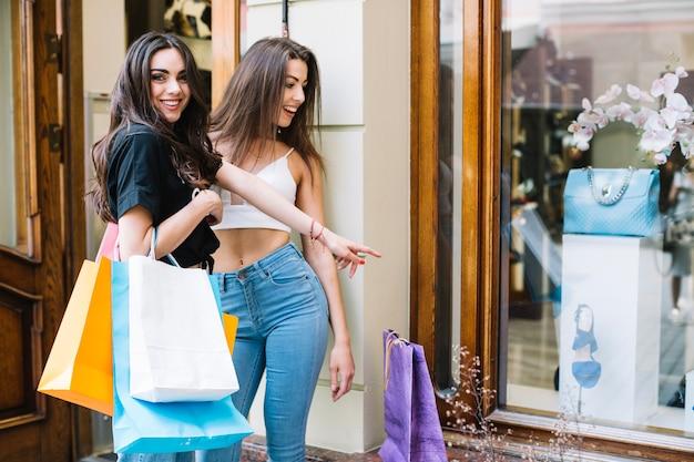 Happy women lookin at bag behind shop-window Free Photo