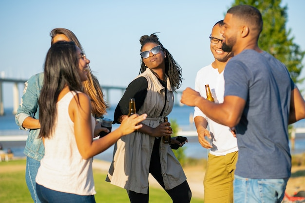Happy women and men dancing in park in evening. cheerful friends relaxing with beer during sunset. leisure concept Free Photo
