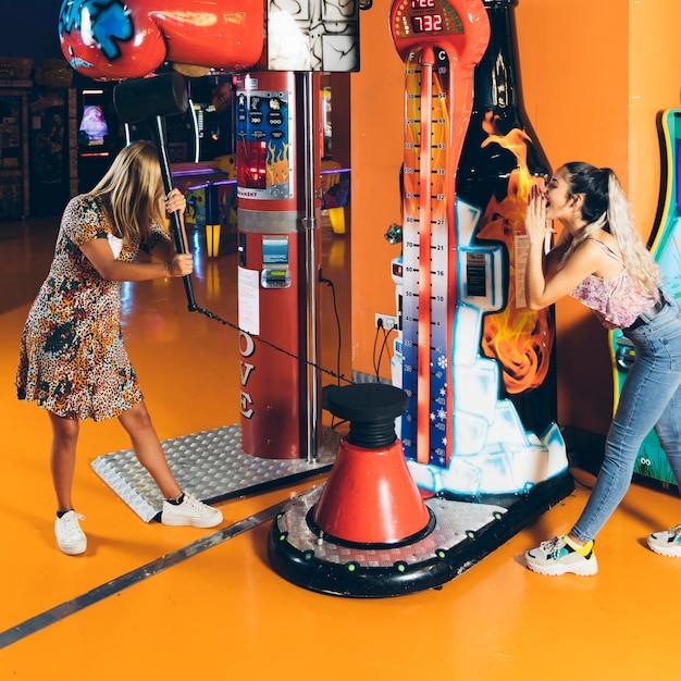 Happy women playing arcade game Free Photo