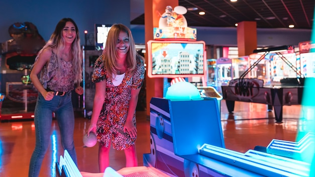 Happy women playing arcade game Free Photo