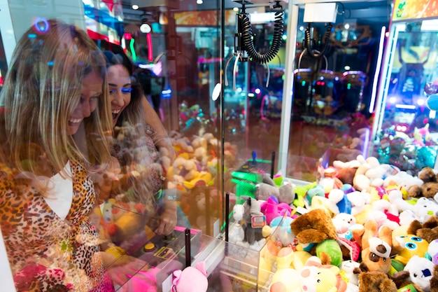 Happy women playing arcade machine Free Photo