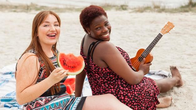 Счастливые женщины позируют на пляже с арбузом и гитарой Бесплатные Фотографии