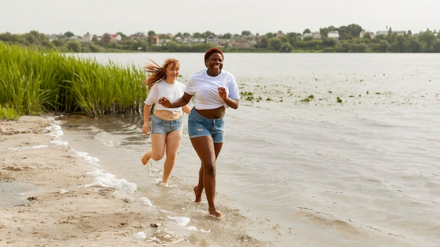 Happy women running together at the beach Free Photo